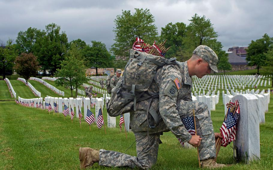 First Lt. David Harper of The Old Guard places an American flag at a headstone during the Flags-In at Arlington National Cemetery on Thursday, May 21, 2015, in Arlington, Va.