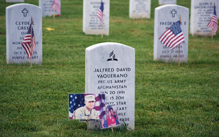 American flags are seen placed at headstones in Arlington National Cemetery in Arlington, Va., on Thursday, May 21, 2015, as part of the Flags-In event.