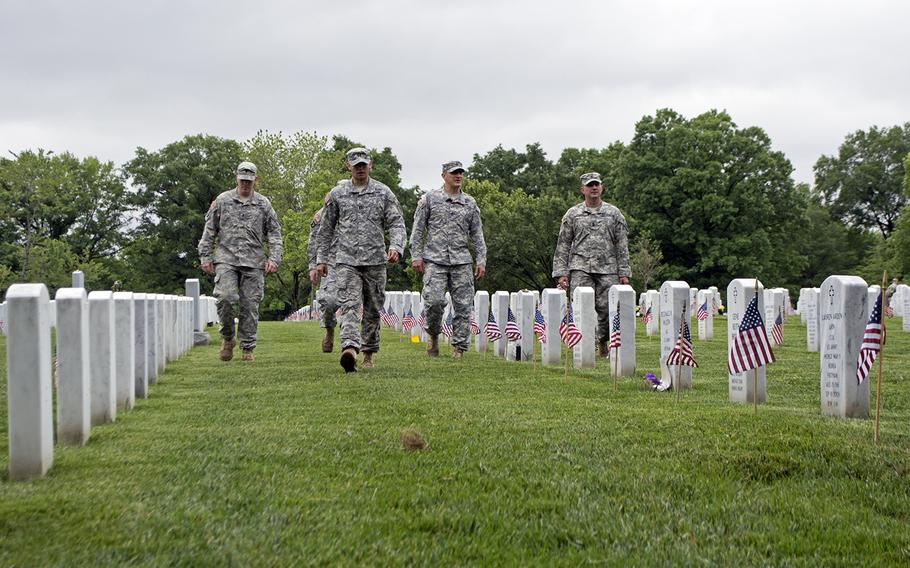 Members of The Old Guard looks more flags and more empty headstones toward the end of the Flags-In at Arlington National Cemetery on May 21, 2015.