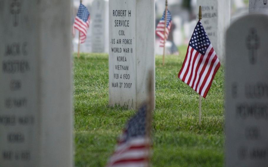 A rose rests near an American flag at a headstone at Arlington National Cemetery Thursday, May 21, 2015, during Flags-In. Every headstone received an American flag by the Old Guard.