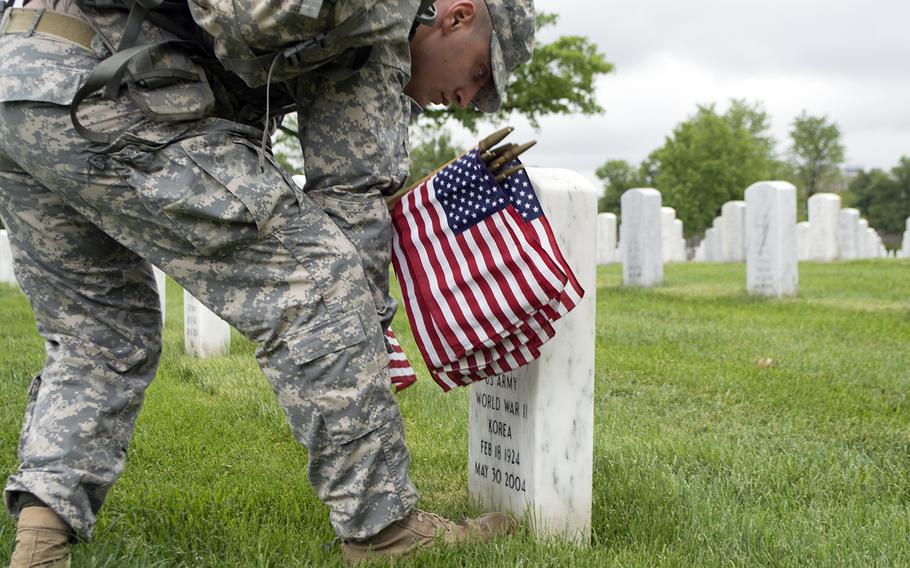 A member of The Old Guard places an American flag at a headstone during the Flags-In at Arlington National Cemetery on May 21, 2015.