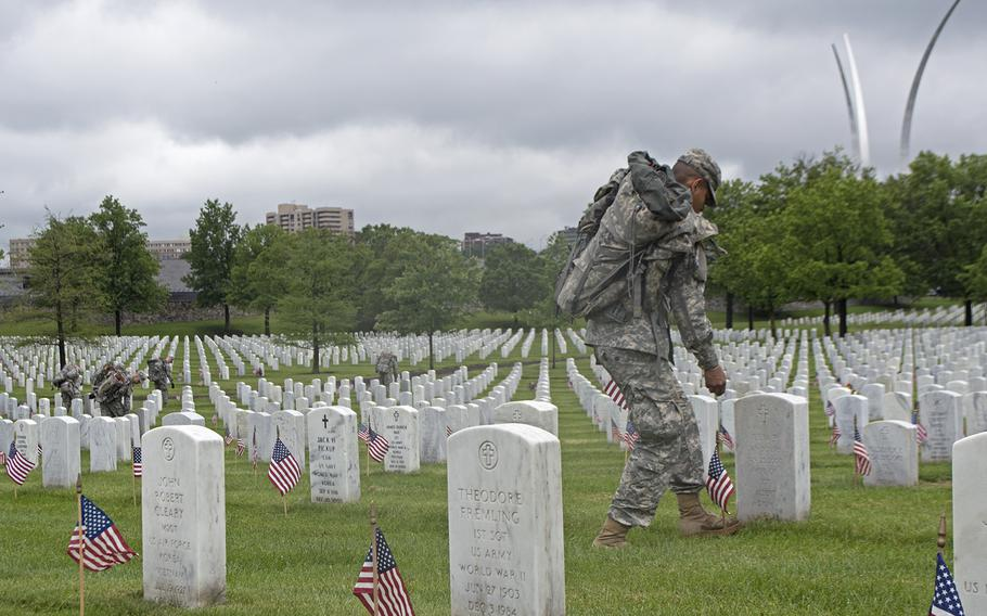 A member of The Old Guard places an American flag at a headstone during the Flags-In at Arlington National Cemetery on May 21, 2015. The Air Force Memorial can be see in the background.