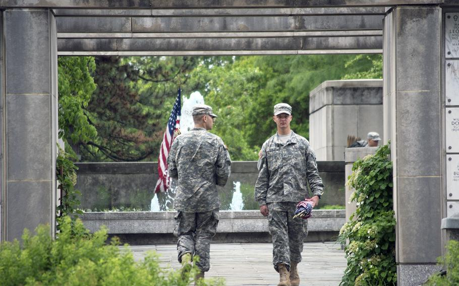 Members of The Old Guard looks more flags and more empty headstones toward the end of the Flags-In at Arlington National Cemetery on May 21, 2015, inside the columbarium.
