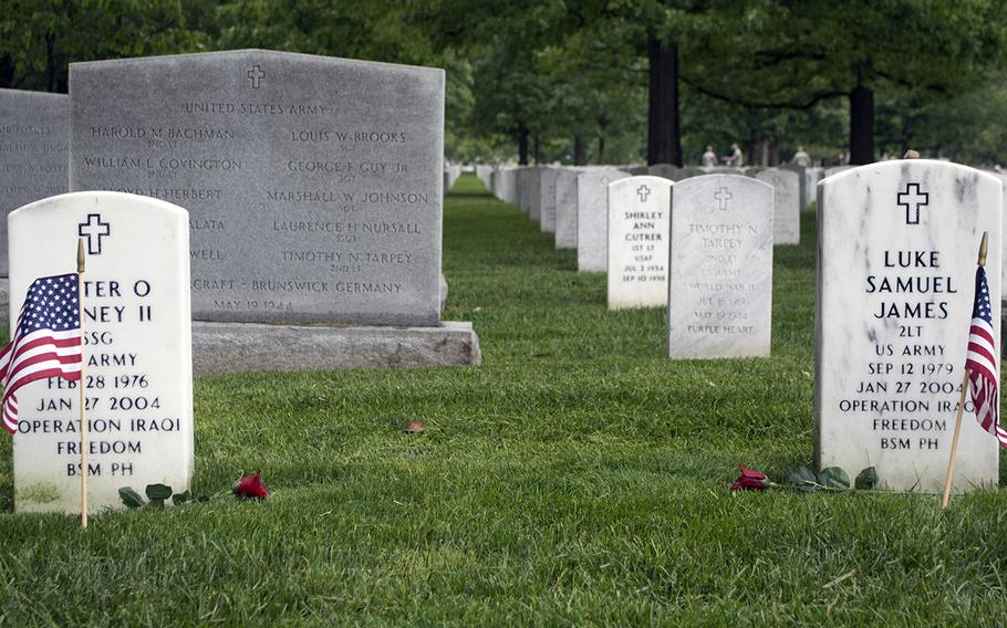 Roses rest near American flags placed at headstones in Arlington National Cemetery during the Flags-In on May 21, 2015.