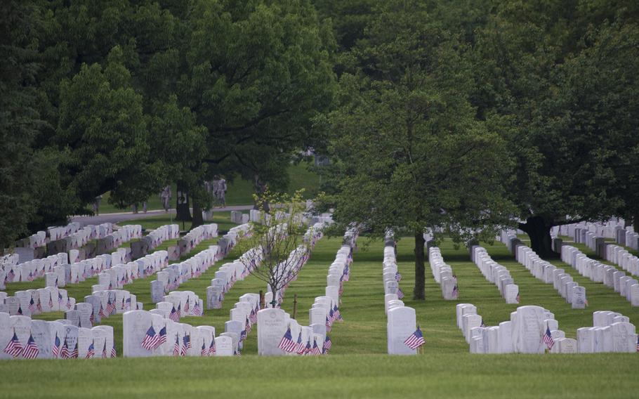 Shadows start to darken the headstones at Arlington National Cemetery Thursday, May 21, 2015, as Flags-In ends. Every headstone received an American flag by the Old Guard, some of which can be partially seen behind the trees.