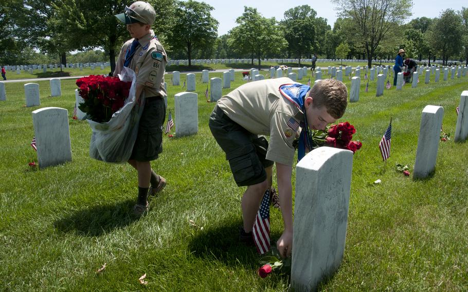 Boy Scounts Jerry Dalrymple (right) and Liam Kellogg (left) of Troop 884 out of Manassas, Va., help lay roses at gravestones at Arlington National Cemetery for Memorial Day on May 24, 2015.