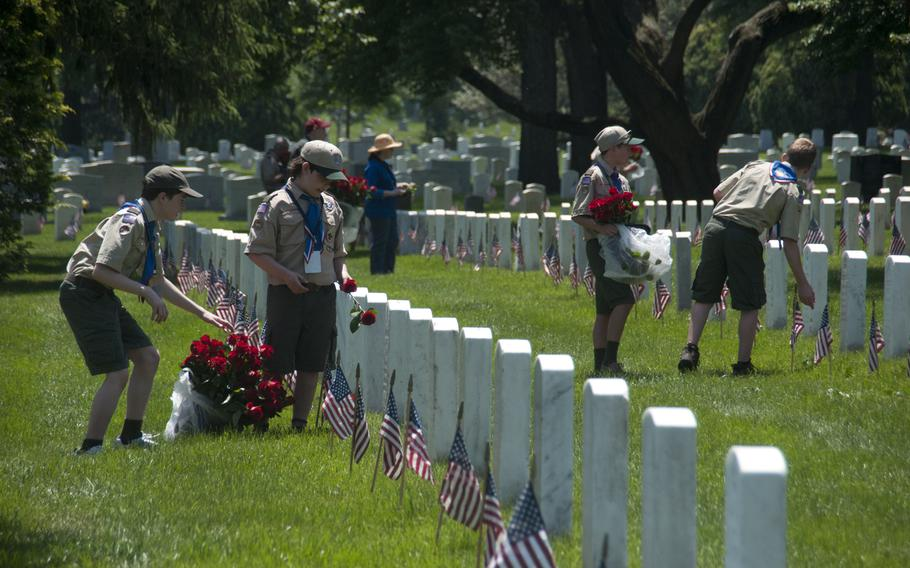 Boy Scouts help lay roses at gravestones at Arlington National Cemetery for Memorial Day on May 24, 2015.