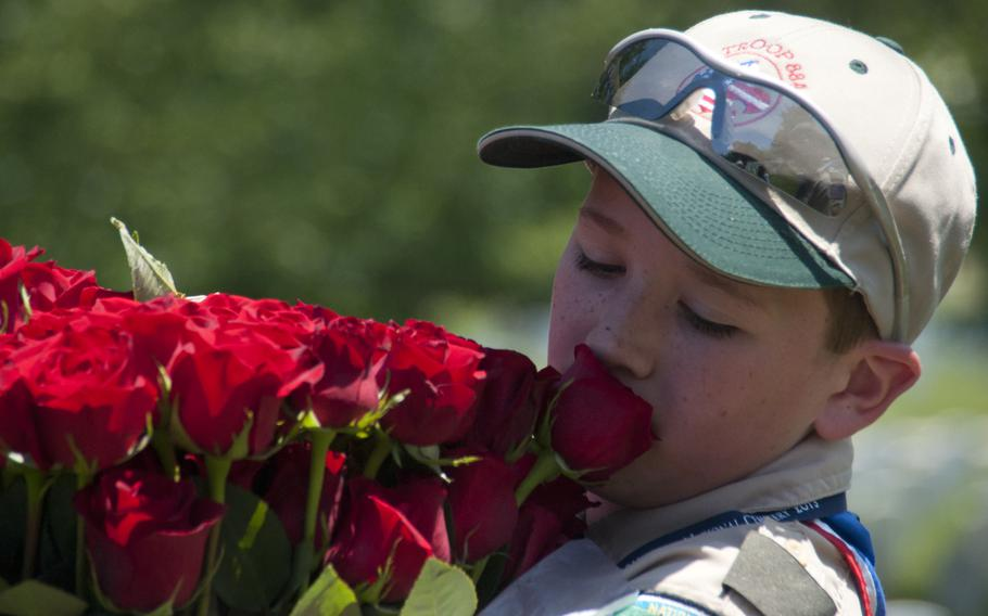 Boy Scout Liam Kellogg of Troop 884 helps lay roses at gravestones at Arlington National Cemetery for Memorial Day on May 24, 2015.