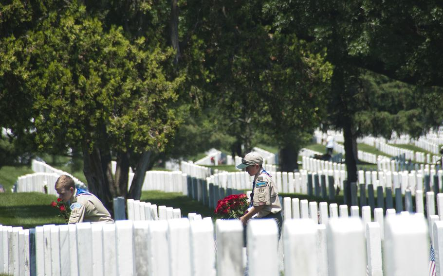 Boy Scouts Jerry Dalrymple (left) and Liam Kellogg, of Troop 884 out of Manassas, Va., help lay roses at gravestones at Arlington National Cemetery for Memorial Day on May 24, 2015.