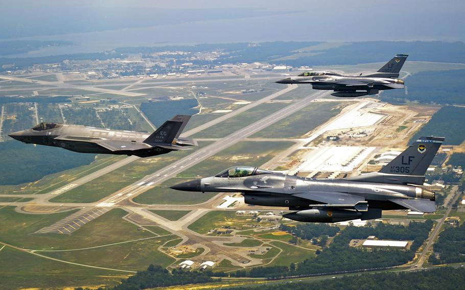 In a July, 2011 file photo, DOD's first F-35 Lightning II joint strike fighter soars past the 33rd Fighter Wing flightline with two F-16 Fighting Falcon chase aircraft before landing at its new home at Eglin Air Force Base, Fla.