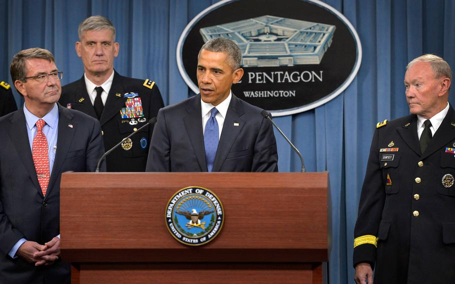 President Barack Obama addresses reporters in a rare appearance at the Pentagon in Washington on Monday, July 6, 2015, flanked by Defense Secretary Ash Carter, left, and Joint Chiefs Chairman Gen. Martin E. Dempsey, right.