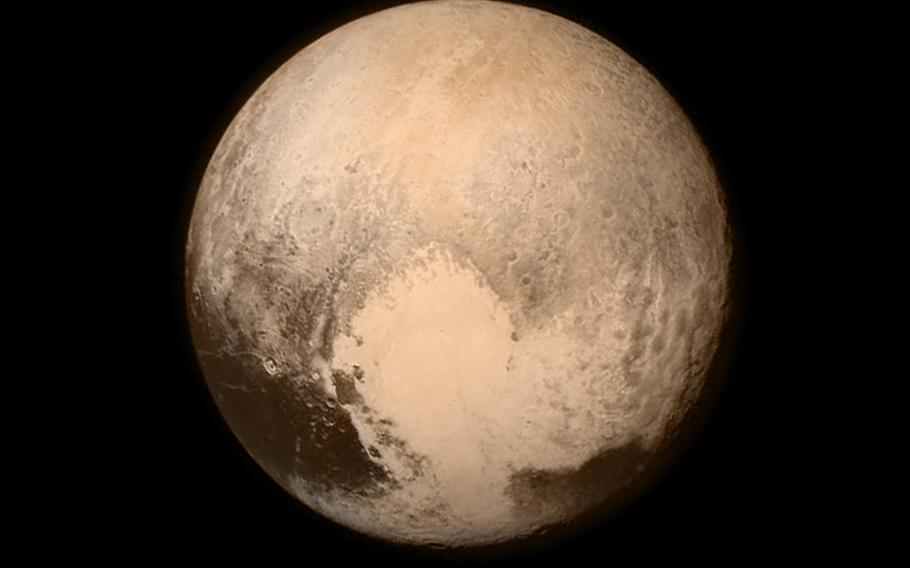 """This New Horizons shot shows off Pluto's """"heart"""" in full color. The spacecraft was just over half a million miles away from the dwarf planet on July 13, 2015. The """"heart"""" measures approximately 1,000 miles across."""