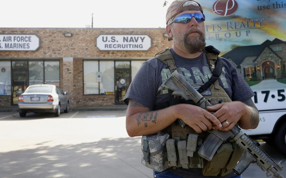 Terry Jackson, a member of Operation Hero Guard, stands guard outside a U.S. military recruiting station in Cleburne, Texas, Tuesday, July 21, 2015.