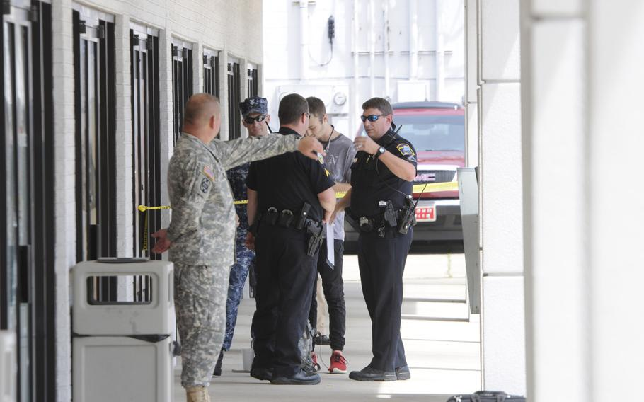 Authorities talk to workers at a Navy and Marine Corps recruitment center in Chattanooga, Tenn., where a gunman opened fire Thursday, July 16, 2015. Yellow tape cordoned off an area with blue shell casing markers in the parking lot.