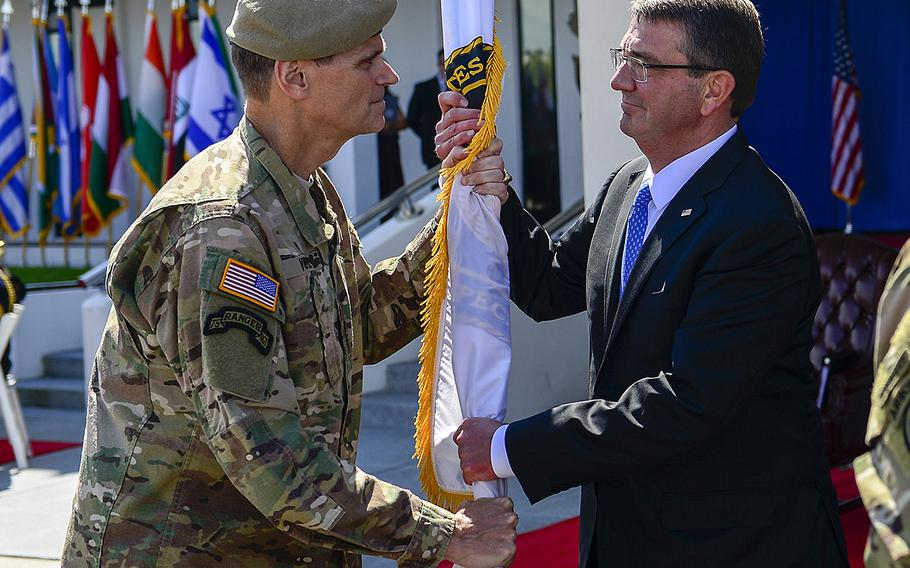 Army Gen. Joseph L. Votel, former commander of U.S. Special Operations Command, passes the guidon to Secretary of Defense, Ashton Carter, during the change-of-command ceremony March 30 at MacDill Air Force Base, Fla.