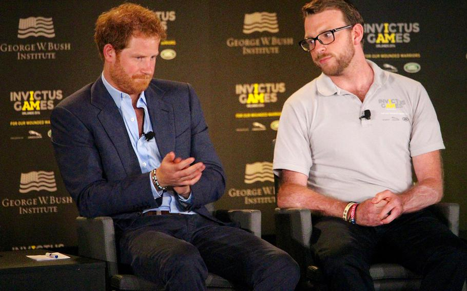 Britain's Prince Harry talks about ways to help returning servicemen who have suffered traumatic injuries on the battlefield as Lance. Cpl. John-James Chalmers, formerly of the Royal Marines Commando, listens during the 2016 Invictus Games Symposium on Invisible Wounds, Sunday, May 8, 2016 at Orlando, Fla.
