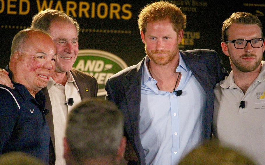 From left, Master Sgt. Israel Del Toro, Jr., former President George W. Bush, Britain's Prince Harry and Lance Cpl. John-James Chalmers, formerly of the Royal Marines Commando, pose for pictures after speaking on a panel at the 2016 Invictus Games Symposium on Invisible Wounds, Sunday, May 8, 2016 at Orlando, Fla.