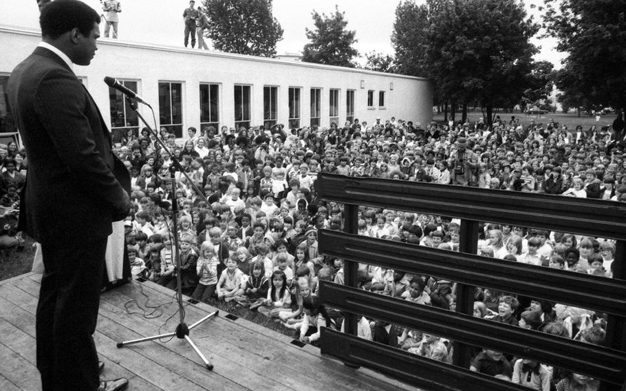 Muhammad Ali talks to a crowd of more than 1,200 fascinated schoolkids at the Augsburg American School in May, 1976. After visiting the school, Ali attended a race-relations class where he lectured on the need for mankind to return to the teachings and abide by the laws of God.