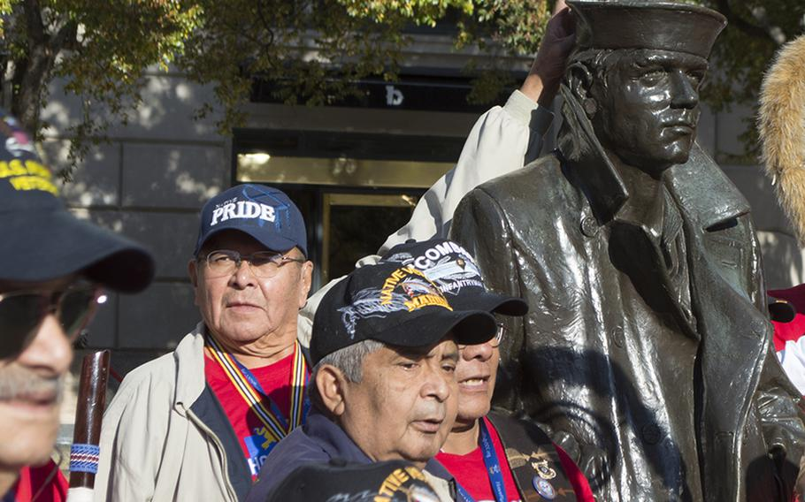 A Native American veteran gives the Lone Sailor bunny ears while waiting for a group shot during the first Native American Honor Flight in Washington, D.C. at the US Navy Memorial.