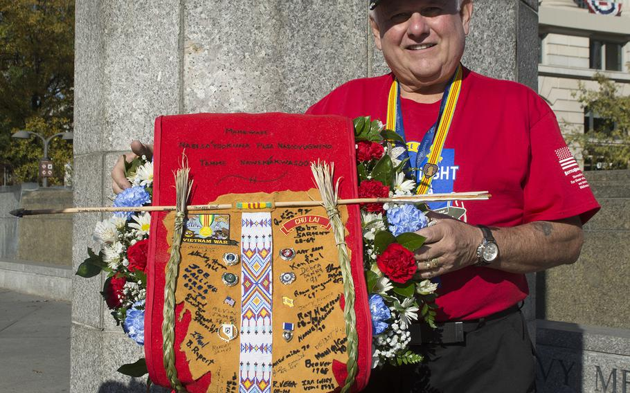 Bob Tilton poses at the US Navy Memorial with the wreath and the banner he created on Veterans Day in Washington, D.C. Tilton was part of the first Native American Honor Flight and they were placing the wreath later in the afternoon during a ceremony at the Vietnam Wall.