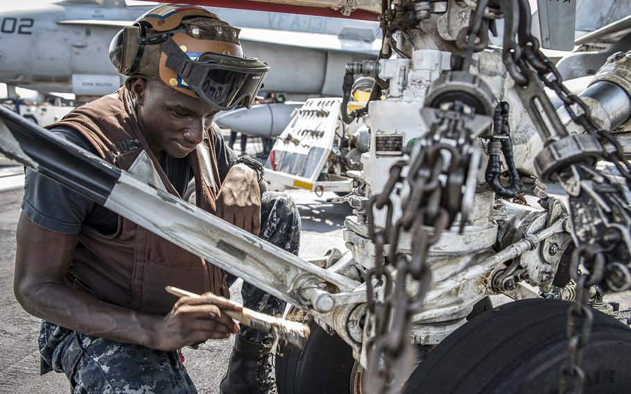 In a September, 2016 file photo, Airman Holguy Rinchet cleans the landing gear of an F/A-18C Hornet assigned to Strike Fighter Squadron 131 on the flight deck of the aircraft carrier USS Dwight D. Eisenhower in the Persian Gulf.