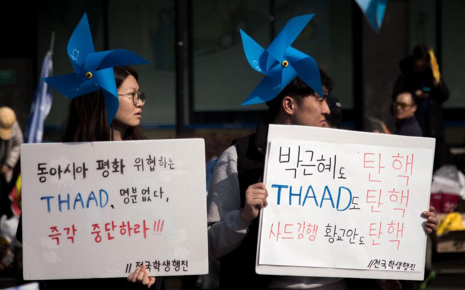 Protesters march by the U.S. Embassy at Gwanghwamun Square, Seoul, South Korea, Saturday, March 11, 2017.