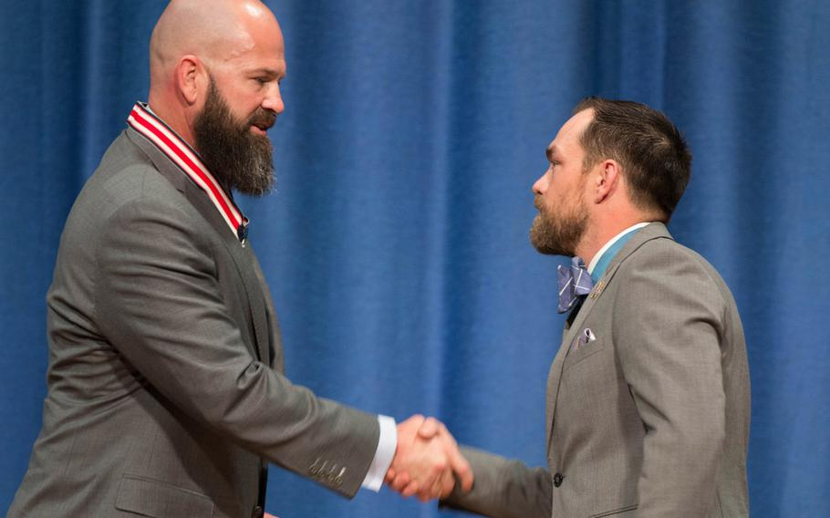 Travis Ellis, left, shakes hands with Medal of Honor recipient Clinton Romesha on Saturday, March 25, 2017. Ellis received the Citizens Honors Award, the highest given by the Congressional Medal of Honor society, for his work in combating PTSD and traumatic brain injury in servicemembers.