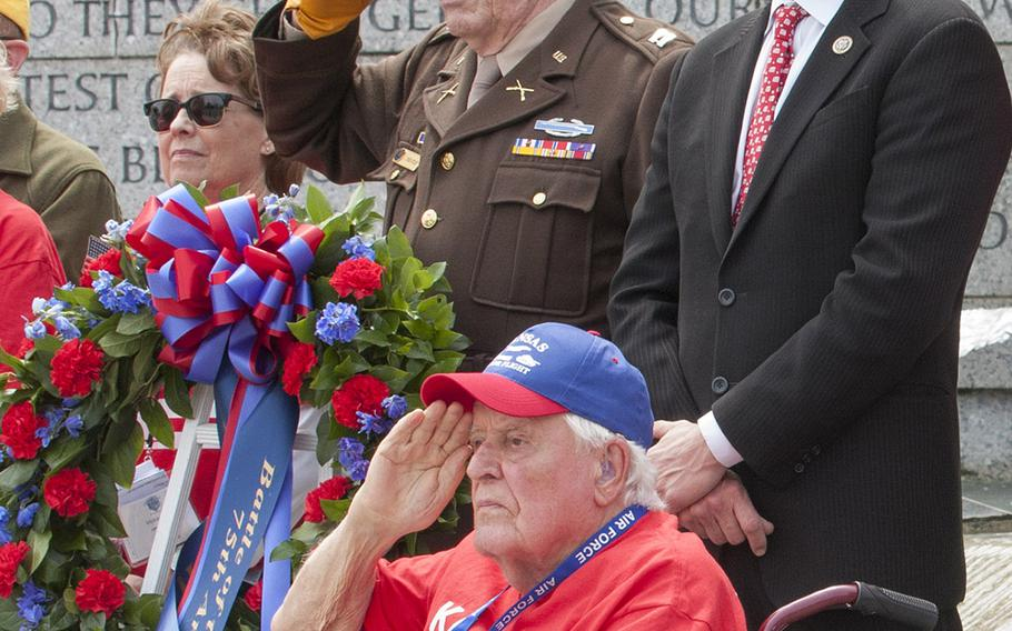 Rep. Roger Marshall, R-Kan., at right, closes his eyes during taps while WWII, Korea and Vietnam veteran Ewin Aley, foreground, salutes at the Battle of the Coral Sea 75th Anniversary at the World War II Memorial in Washington, D.C., on May 4, 2017.