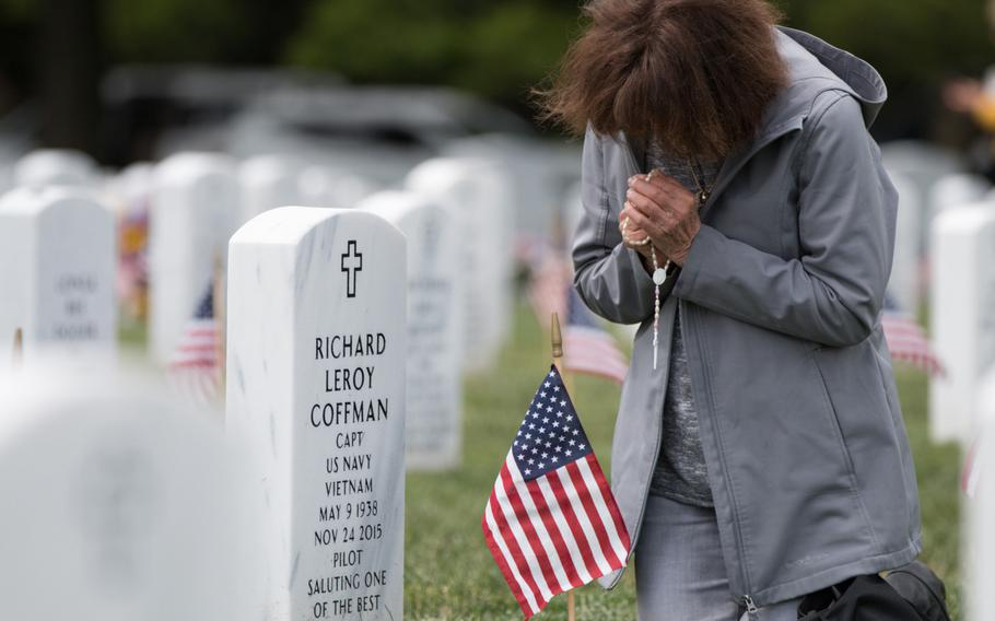 """J'Neane Coffman prays at the grave marker of her husband, Richard """"Skip"""" Coffman, during Flags In at Arlington National Cemetery on May 25, 2016."""