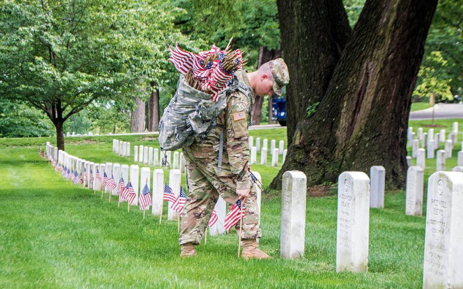 A soldier with the 3rd U.S. Infantry Regiment (The Old Guard) places a flag at Arlington National Cemetery during the Flags In on May 25, 2017. Flags In has taken place every year since The Old Guard was designated as the Army's official ceremonial unit in 1948.