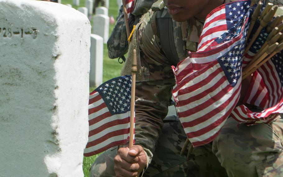 A soldier with the 3rd U.S. Infantry Regiment (The Old Guard) places a flag at Arlington National Cemetery during Flags In on May 25, 2017.