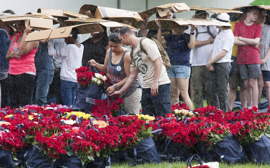Volunteers pick up bags of roses to be placed at Arlington National Cemetery graves as others waiting to register seek shelter from a sudden downpour during an event organized by the Memorial Day Flowers Foundation on Sunday, May 28, 2017.