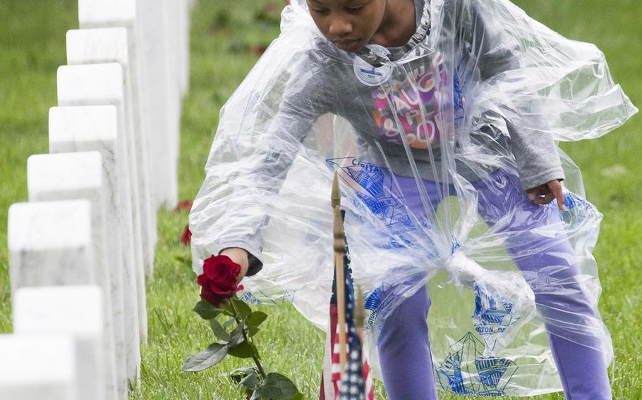 Six-year-old Liana Danner places a rose at an Arlington National Cemetery grave during an event organized by the Memorial Day Flowers Foundation on Sunday, May 28, 2017.