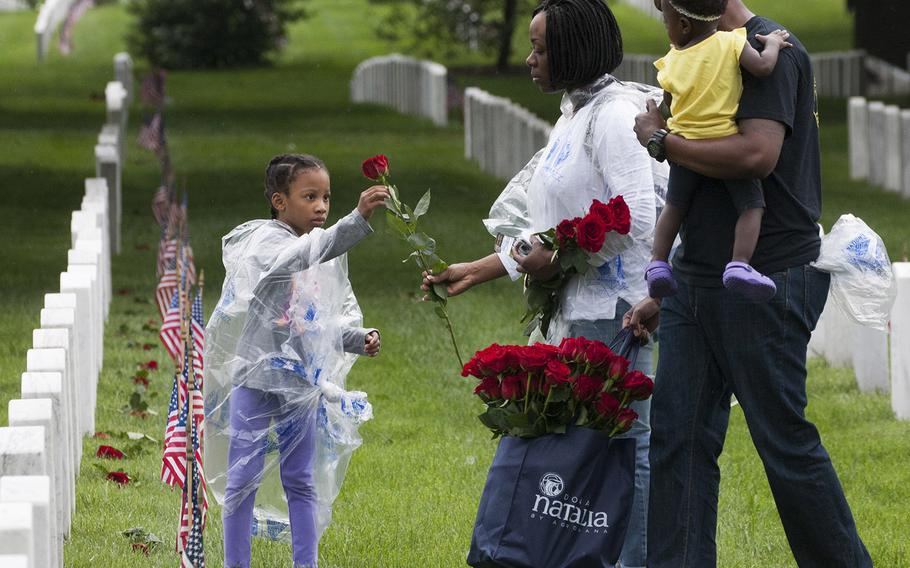 U.S. Marine Corps Staff Sgt. Angelica Danner hands a rose to six-year-old Liana Danner to place at an Arlington National Cemetery grave as Marine Staff Sgt. Marvin McCammon, holding Mikayla McCammon, watches during an event organized by the Memorial Day Flowers Foundation on Sunday, May 28, 2017.