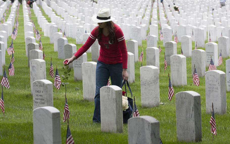 Asa Meyer of Arlington, Va. places a rose at an Arlington National Cemetery during an event organized by the Memorial Day Flowers Foundation on Sunday, May 28, 2017. Meyer said it's the fifth year she's taken part in the event.