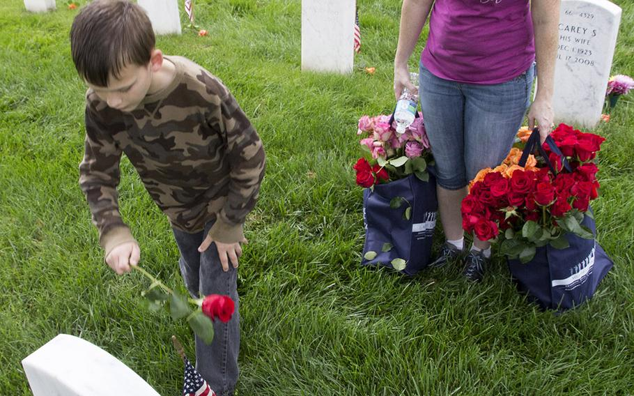 Volunteers place roses at an Arlington National Cemetery grave during an event organized by the Memorial Day Flowers Foundation on Sunday, May 28, 2017.