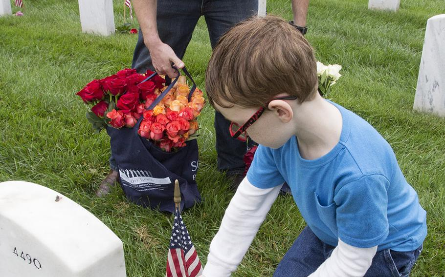 Seven-year-old Chase Halstead places a rose at an Arlington National Cemetery grave as his dad, U.S. Marine Corps Staff Sgt. Nathan Halstead, watches during an event organized by the Memorial Day Flowers Foundation on Sunday, May 28, 2017.