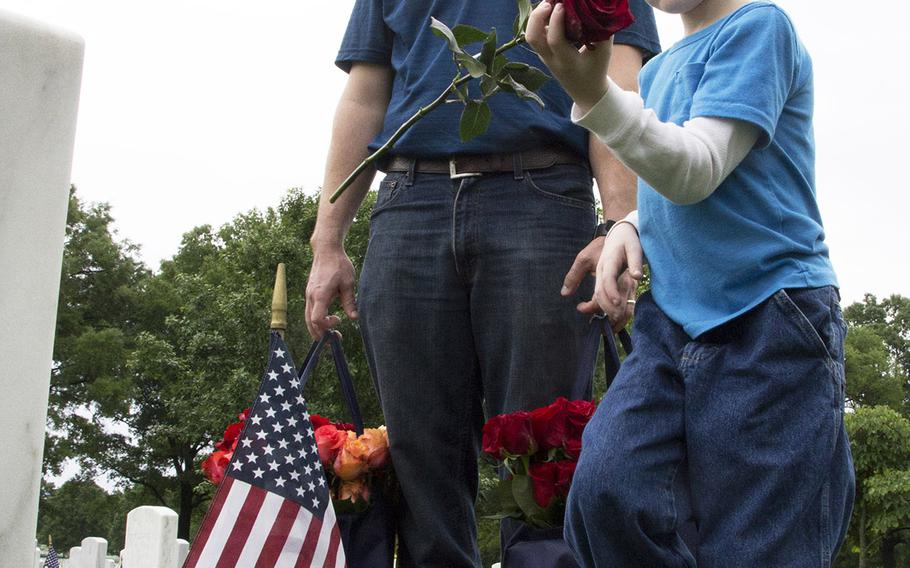 Seven-year-old Chase Halstead prepares to place a rose at an Arlington National Cemetery grave as his dad, U.S. Marine Corps Staff Sgt. Nathan Halstead, watches during an event organized by the Memorial Day Flowers Foundation on Sunday, May 28, 2017.