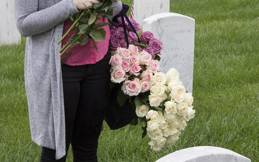 Cathleen Beckman pauses before placing a rose at an Arlington National Cemetery grave during an event organized by the Memorial Day Flowers Foundation on Sunday, May 28, 2017.