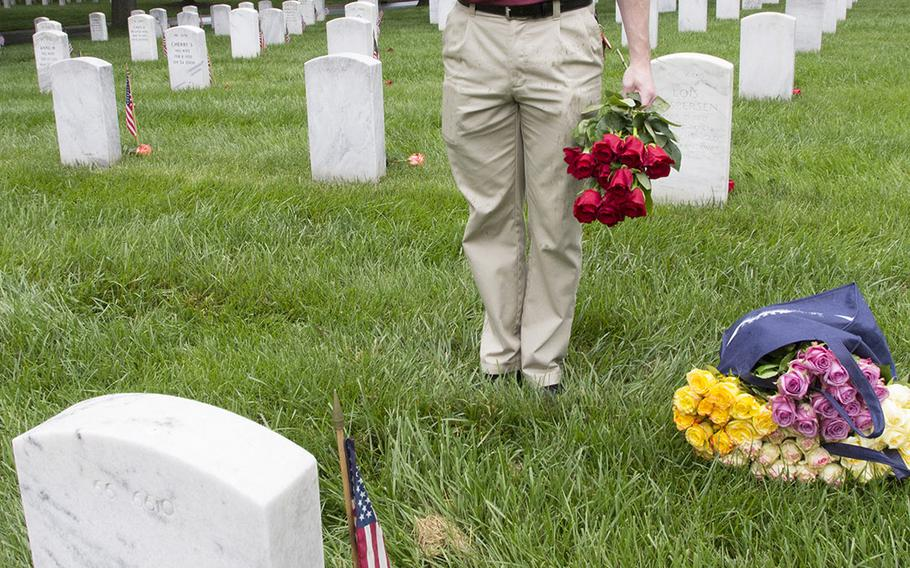 U.S. Army 2nd Lt. Chris Kimrey salutes after placing a rose at an Arlington National Cemetery grave during an event organized by the Memorial Day Flowers Foundation on Sunday, May 28, 2017.