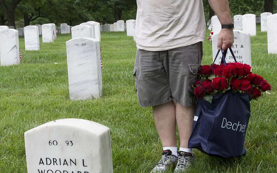 A veteran salutes after placing a rose at an Arlington National Cemetery grave during an event organized by the Memorial Day Flowers Foundation on Sunday, May 28, 2017.