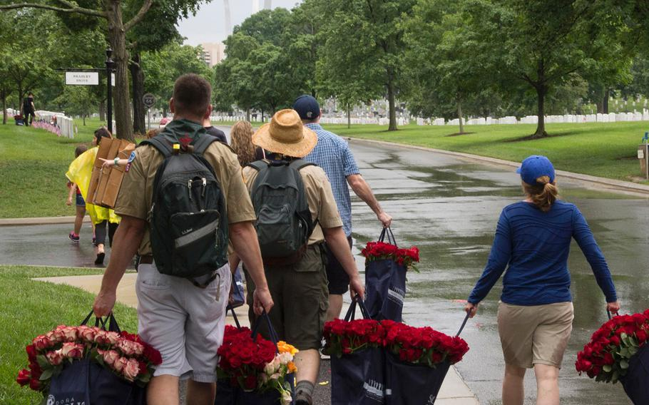 With the U.S. Air Force Memorial in the background, volunteers carry bags of roses to be placed at Arlington National Cemetery graves during an event organized by the Memorial Day Flowers Foundation on Sunday, May 28, 2017.
