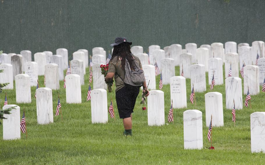 A vlunteer walks through a sudden downpour to place roses on Arlington National Cemetery graves during an event organized by the Memorial Day Flowers Foundation on Sunday, May 28, 2017.