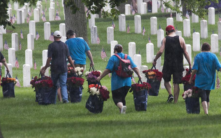 Volunteers carry bags of roses to be placed at Arlington National Cemetery graves during an event organized by the Memorial Day Flowers Foundation on Sunday, May 28, 2017.