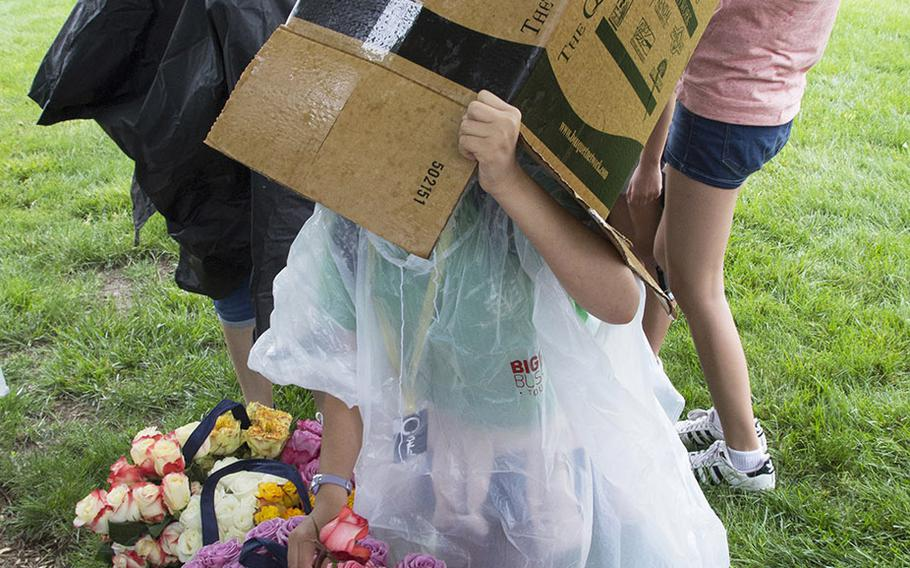 A young volunteer covers herself against a sudden downpour before going out to place roses on graves at Arlington National Cemetery during an event organized by the Memorial Day Flowers Foundation on Sunday, May 28, 2017.