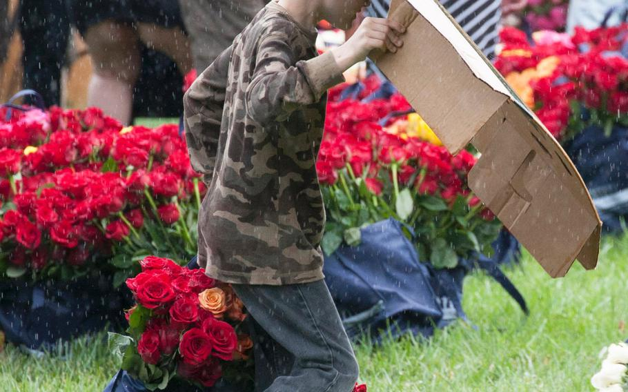 A young volunteer shields himself against a sudden downpour as he carries roses to be placed at Arlington National Cemetery graves during an event organized by the Memorial Day Flowers Foundation on Sunday, May 28, 2017.
