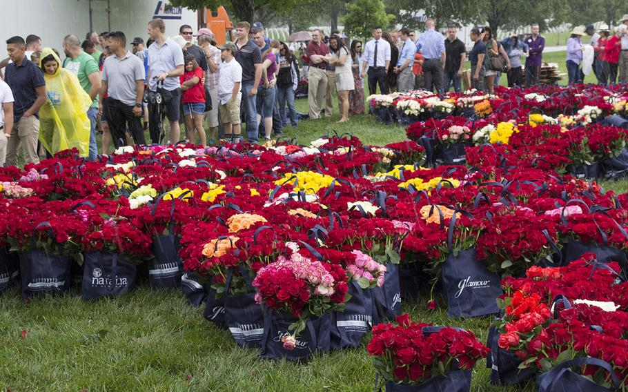 Volunteers line up for roses to be placed at Arlington National Cemetery graves during an event organized by the Memorial Day Flowers Foundation on Sunday, May 28, 2017.