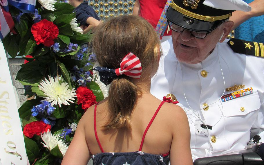 Jim Downing, a 103-year-old World War II Navy veteran, speaks with a young girl following the Memorial Day event at the World War II Memorial in Washington on Monday, May 29, 2017. Downing is the second oldest living Pearl Harbor survivor.