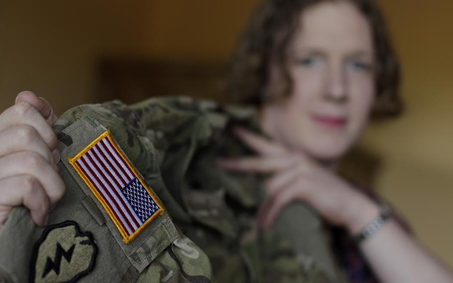 In this July 29, 2017, photo, transgender U.S. Army Capt. Jennifer Sims lifts her uniform during an interview with The Associated Press in Beratzhausen near Regensburg, Germany.