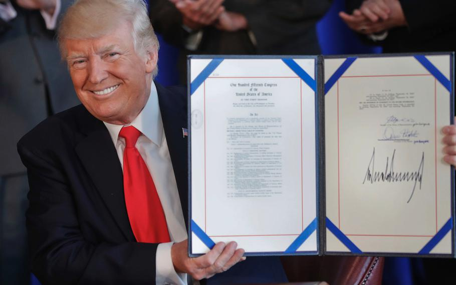 President Donald Trump smiles after signing the Veteran's Affairs Choice and Quality Employment Act of 2017 at Trump National Golf Club in Bedminister, N.J., Saturday, Aug. 12, 2017.